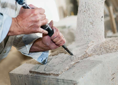 craft on marble: Man carves the marble with the chisel