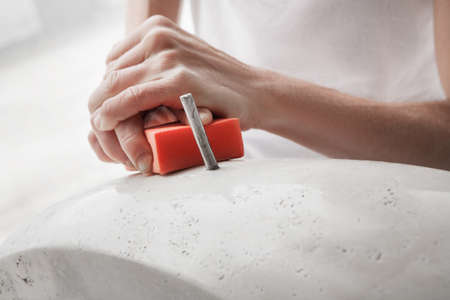 stone cutter: girls hands to smooth pieace of marble Stock Photo