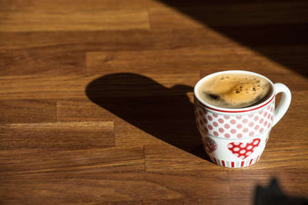 cup of coffee on a wooden deskwith the early morning light and long shadows