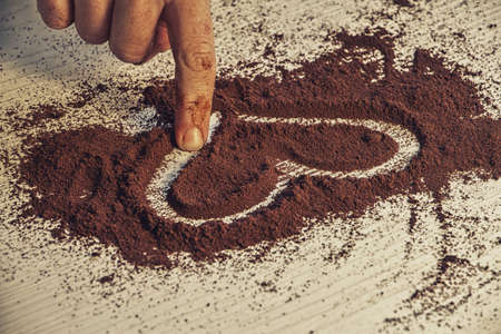 girl draws a heart with her finger in the ground coffee