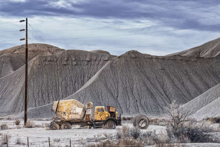 an abandoned cement mixer with politically motivated graffiti in the Utah desert in a context of neglect and squalor