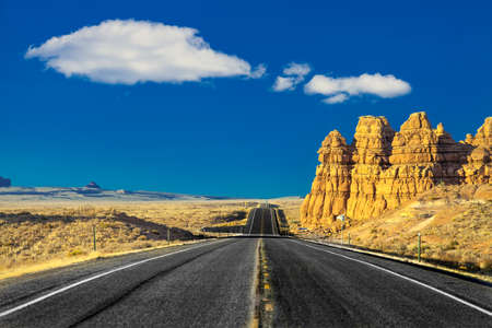 on the road in the desert of rocks and mountains in the United States in Utah with blue sky and clouds