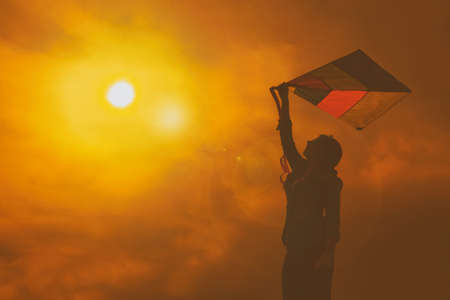 backlit girl holds in her hands a kite during sunset with an orange sky and dramatic effect Stock Photo