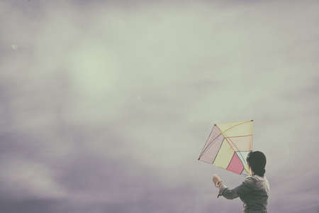 girl holds in her hands a kite with a cloudy blue sky and drama