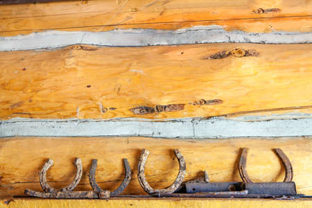 Rusted horseshoes Placed on a shelf with a wooden wall background