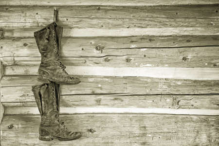 a pair of boots hanging from a wooden wall in a rustic cottage