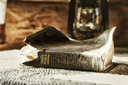 worn and old holy bible on a table with a lantern in the background Stock Photo
