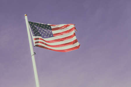 american flag waving in the blue sky, the stars and stripes with white pole Stock Photo