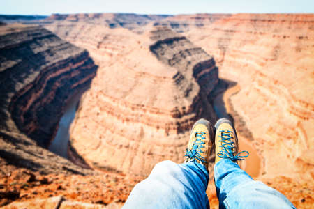 PHOTOS IN FIRST PERSON OF A couple of feet with shoes OF A BOY STANDING ON TOP OF A MOUNTAIN - GOOSENECK CANYON PARK IN UTAH USA