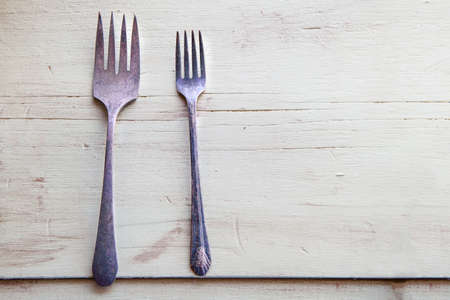 a pair of old forks on a green wooden table, Victorian era in the United States of the old westerns