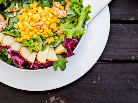 Artistic bowl of fresh corn and seafood salad served in a restaurant with pink prawn or shrimp, apple, red cabbage, lettuce, maize and rocket viewed from above Stock Photo