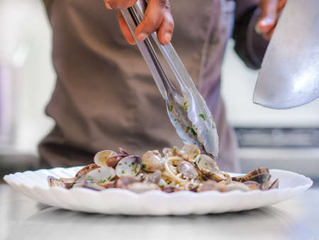 Chef plating up freshly cooked clams in sauce from a metal frying pan onto a plate using tongs in a low angle view Stock Photo