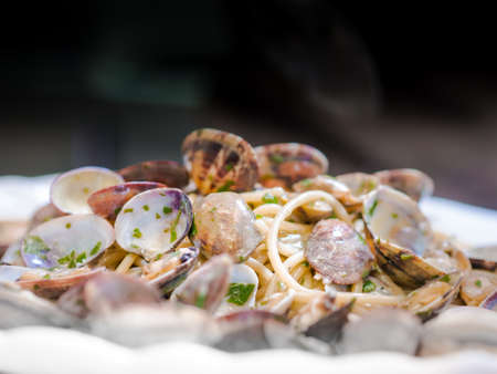 Serving of clams and savory sauce garnished with chopped parsley on Italian pasta or noodles in a low angle view on the plate