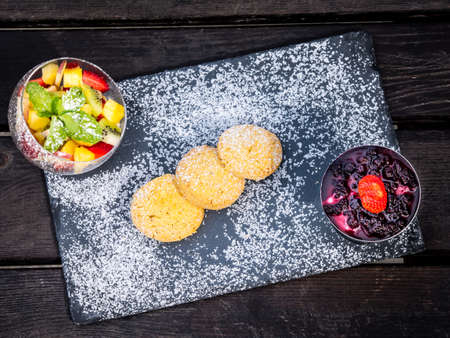 Gourmet presentation of fresh fruit dessert with bowls of mixed fruit salad and berries and fresh baked cookies on a board sprinkled with sugar