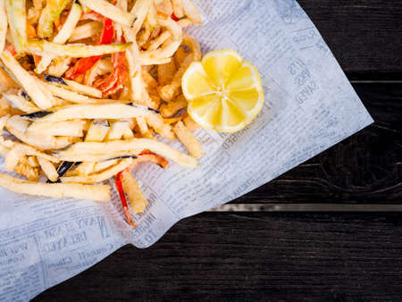 Overhead view of French fries and lemon on white serviette Stock Photo