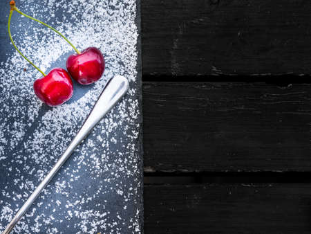 Two fresh red cherries on a dessert board sprinkled with sugar and served with a silver spoon viewed from above with copy space