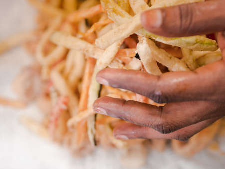 African woman forming a mound of fresh vegetable chips with her hand as she plates up food in a restaurant in a close up view Stock Photo