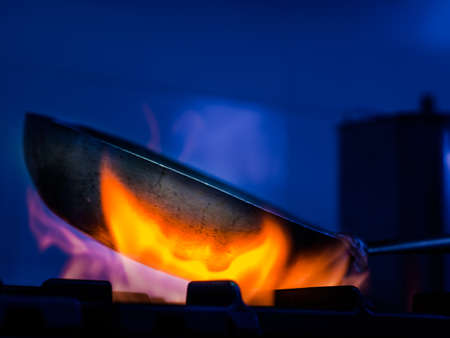 Heating a sizzling frying pan over a gas burner while cooking in the kitchen in a low angle view of the fiery orange flames, steam and pan