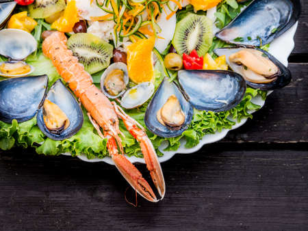 Mixed seafood platter with assorted shellfish including clams, mussels and langoustine or lobster served on a bed of fresh salad viewed from above on a table with copy space