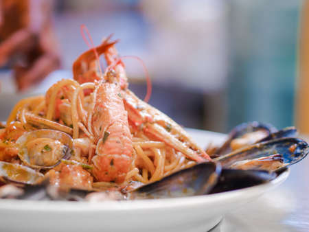 Serving of plated gourmet seafood pasta with clams and langoustine or lobster with marine mussels to the side in a low angle side view with copy space Stock Photo