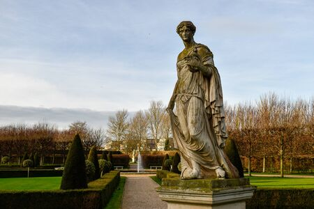 Sculpture of a woman in a european garden which can be seen in the background. Great for use as a concept to describe european culture and history