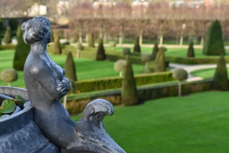 A close up view of a sculpture of a woman in a european garden which can be seen in the background. Great for use as a concept to describe european culture and history