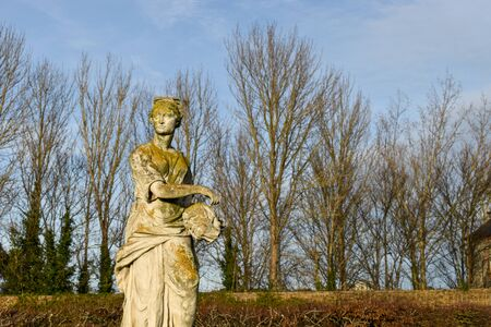 a sculpture of a woman in a european garden