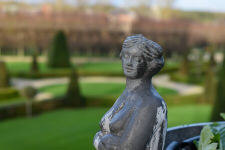 A close up view of a sculpture of a woman in a european garden which can be seen in the background