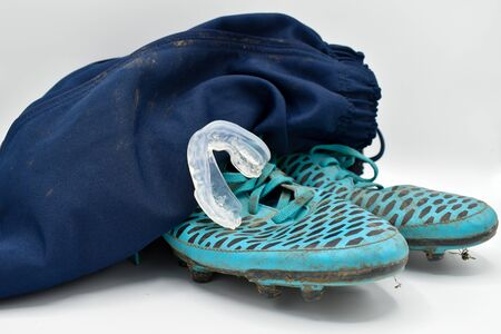 dirty rugby gear on a white background. Rugby boots, shorts and gumshield mouthguard Standard-Bild