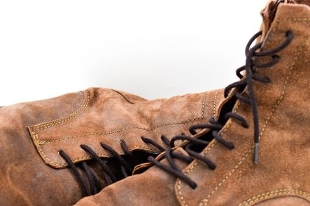 close up of a pair of brown mens leather boots isolated on white background