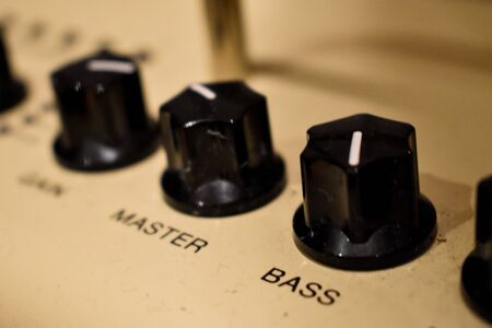 Close up of control knobs on an amp or amplifier for electric and bass guitars
