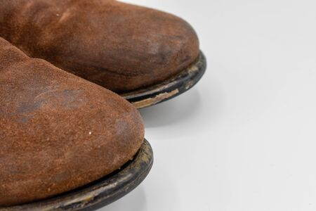 close up of the toes of a pair of brown mens leather boots isolated on white background