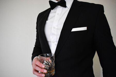 Una vista de cerca de un hombre con un esmoquin negro sosteniendo un vaso de whisky