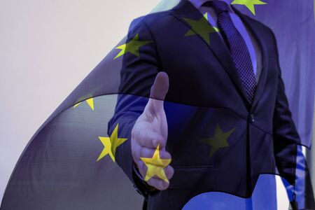 European Politician or Business man open hand ready to seal a deal, shaking hands, EU flag brexit deal concept. European union trade deal.