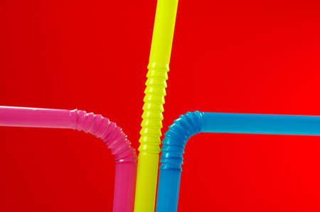 rainbow cocktail: Red Background with close-up of multi colored drinking straw