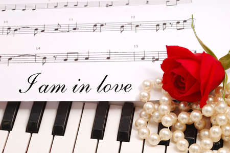 red silky rose with musical notes and a piano photo