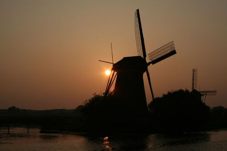 watermanagement: Dutch windmills with setting sun