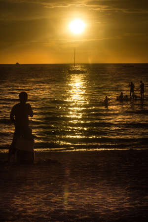 Rippling waves reflect a golden sunset over the sparkling island beach