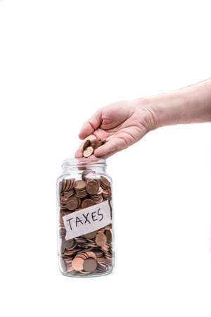 monies: Pouring Change Into a Jar Marked Taxes Stock Photo