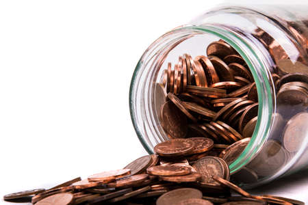 monies: British Penny Coins Spilling From A Jar