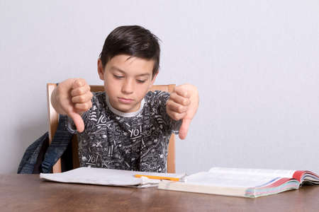 boy 12 year old: Young Boy Doing His Homework Reacting With Thumbs Down