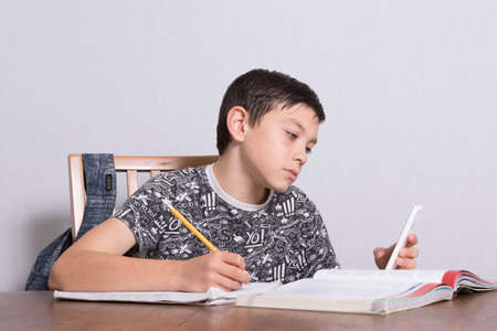 10 to 12 years old: Young Boy Doing His Homework