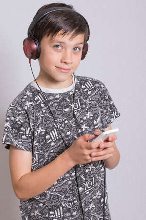 7 year old boys: Young Boy Listening To Music With Headphones Stock Photo