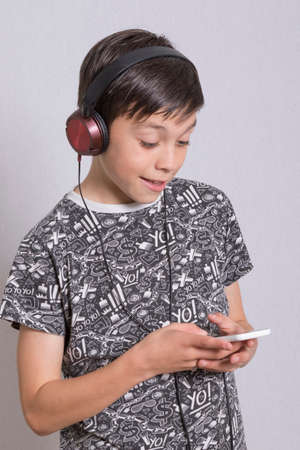 10 to 12 years old: Young Boy Listening To Music With Headphones Stock Photo