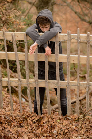 Teenage Boy Leaning On A Fence