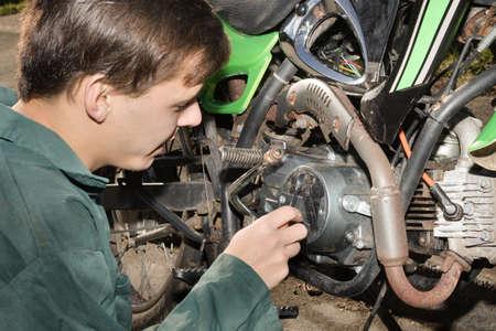 16 to 17 years old: Teenage Boy Working On A Motorbike