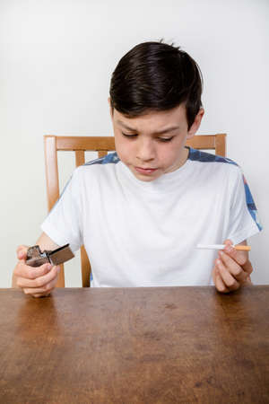 12 13: Young boy thinking about smoking a cigarette while holding a lighter