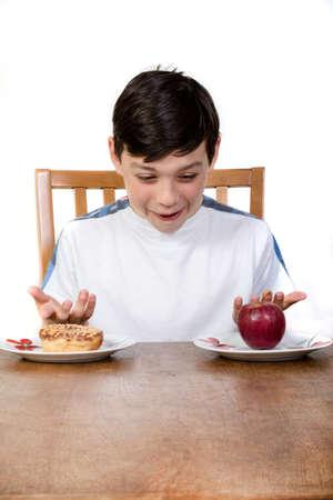ドーナツ、食べてどれを決定するリンゴを見て若い 10 代の少年。 写真素材