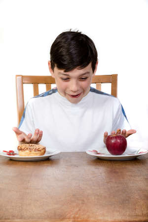 12 13: A young teenage boy looking at a donut and an apple deciding which one to eat. Stock Photo