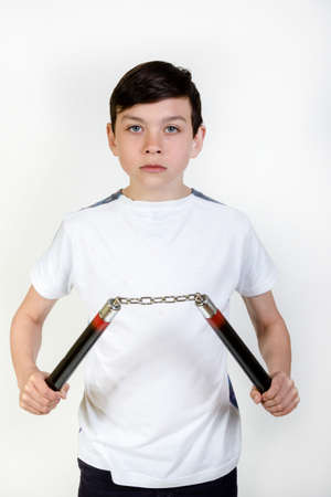 12 13: Young boy holding a pair of Nunchaku